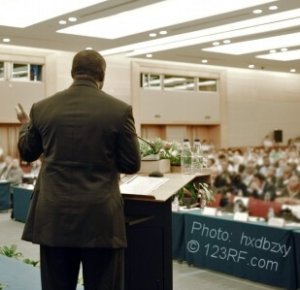 man speaking to a crowd at a conference or business event