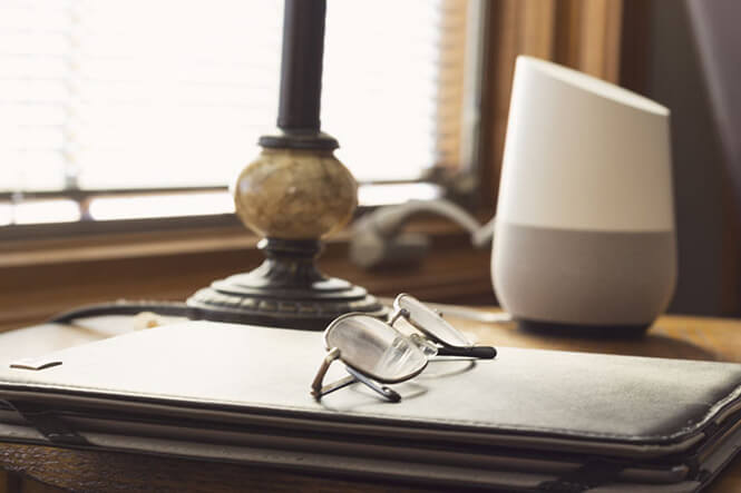 google home on a work desk by the window